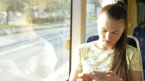 Portrait of attractive serious girl in train using smartphone chatting with friends woman. Slow motion