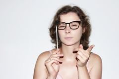 Portrait of attractive sexy brunette woman with mask of glasses on stick. Pretty girl points finger. And chooses on white background. Caucasian woman with Stock Photo