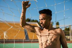 Portrait of attractive shirtless African American sportsman thoughtfully looking away in football goal at stadium