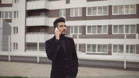 Portrait of attractive slender businessman in formal suit talking on smartphone against the backdrop of business center.  royalty free stock images