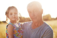 Portrait of attractive small girl poses together with her senior grandfather against nature background, enjoy sunny day during sum Royalty Free Stock Image