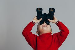 Portrait of attractive smiling boy in red sweater looking through black binoculars close-up stock photos