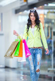 Portrait of the attractive smiling brunette in shopping mall with a bags credit card in a hand Stock Image