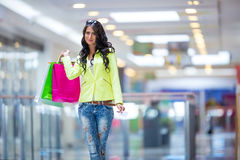 Portrait of the attractive smiling brunette in shopping mall with a bags credit card in a hand Royalty Free Stock Photos