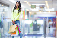 Portrait of the attractive smiling brunette in shopping mall with a bags credit card in a hand Stock Images