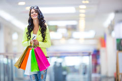 Portrait of the attractive smiling brunette in shopping mall with a bags credit card in a hand Royalty Free Stock Photography