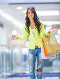 Portrait of the attractive smiling brunette in shopping mall with a bags credit card in a hand Royalty Free Stock Images