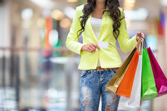 Portrait of the attractive smiling brunette in shopping mall with a bags credit card in a hand Royalty Free Stock Photo