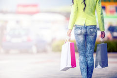 Portrait of the attractive smiling brunette in shopping mall with a bags credit card in a hand Stock Photos