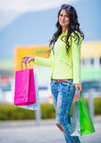 Portrait of the attractive smiling brunette in shopping mall with a bags credit card in a hand Stock Photography