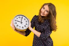 Brunette woman with clocks. Portrait of attractive smiling brunette woman holding clocks isolated on yellow backgroung punctuality or being late concept royalty free stock photos
