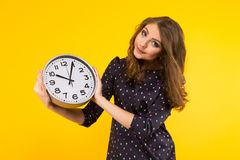 Brunette woman with clocks. Portrait of attractive smiling brunette woman holding clocks on yellow backgroung punctuality or being late concept royalty free stock photos