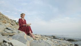 Portrait of attractive smiling caucasian girl in a summer red dress and a straw hat sits with a book in her arms on the. Stones of the sea shore. Flips through stock video footage