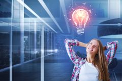Idea and innovation concept. Portrait of attractive smiling european woman on blurry office interior background with copy space and polygonal lamp. Idea and stock image