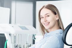 Portrait of an attractive smiling girl blonde in a dental chair. Happy customer dental cabinet stock photos