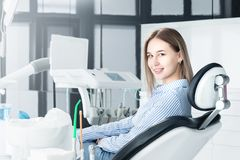 Portrait of an attractive smiling girl blonde in a dental chair. Happy customer dental cabinet royalty free stock photos