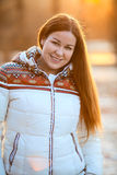 Portrait of attractive smiling woan in white down jacket in sunlight Stock Photography