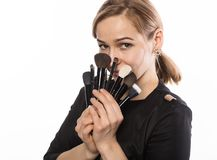 Portrait of attractive smiling woman with brushes for makeup looking at camera a white background Royalty Free Stock Photography