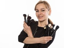 Portrait of attractive smiling woman with brushes for makeup looking at camera a white background Stock Photography