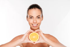 Portrait of attractive smiling woman holding halved orange Stock Image