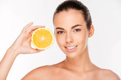 Portrait of attractive smiling woman holding halved orange Stock Photos