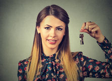 Portrait attractive smiling woman holding up set of keys belonging to her house or car Stock Photos