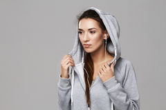 Portrait of attractive sportive girl in hood and headphones posing over white background. Copy space Royalty Free Stock Photo