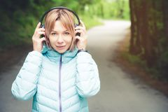 Portrait of an attractive sports girl blonde in a light running down jacket dressing bluetooth headphones with music or. The sounds of nature while on a forest Stock Photo