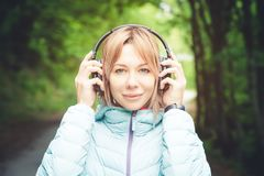 Portrait of an attractive sports girl blonde in a light running down jacket dressing bluetooth headphones with music or. The sounds of nature while on a forest Royalty Free Stock Images