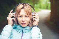 Portrait of an attractive sports girl blonde in a light running down jacket dressing bluetooth headphones with music or. The sounds of nature while on a forest Royalty Free Stock Photography