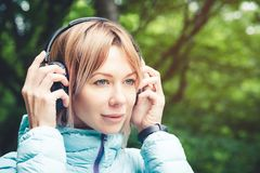 Portrait of an attractive sports girl blonde in a light running down jacket dressing bluetooth headphones with music or. The sounds of nature while on a forest Stock Photos