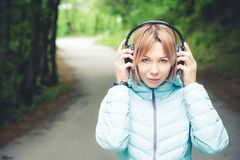 Portrait of an attractive sports girl blonde in a light running down jacket dressing bluetooth headphones with music or. The sounds of nature while on a forest Stock Images