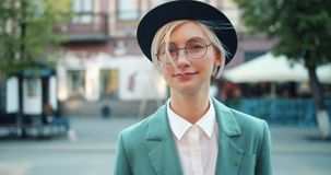 Portrait of attractive student blonde in hat and glasses smiling outdoors stock video footage