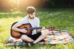 Portrait of attractive stylish bearded guy with guitar sitting crossed legs on green grass, playing musical instrument, enjoying c. Alm atmosphere. Talented boy Stock Photography