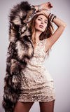 Portrait of attractive stylish woman in fur against grey background. Stock Photos