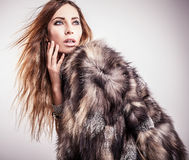 Portrait of attractive stylish woman in fur against grey background. Stock Image