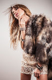 Portrait of attractive stylish woman in fur against grey background. Stock Photography