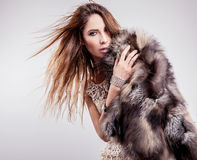Portrait of attractive stylish woman in fur against grey background. Royalty Free Stock Photography