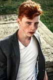 Portrait of attractive stylish young guy model with red hair and freckles sitting on green grass, wearing jacket. Fashionable royalty free stock images