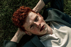 Portrait of attractive stylish young guy model with red hair and freckles sitting on green grass, wearing jacket. Fashionable outd. Portrait of attractive Stock Images
