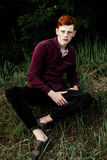 Portrait of attractive stylish young guy model with red hair and freckles sitting on green grass, wearing purple shirt. Fashionabl Royalty Free Stock Image