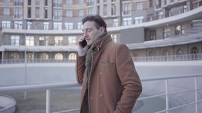 Portrait of attractive successful man in brown coat standing in the city street talking by mobile phone. Urban cityscape. Portrait of handsome confident man in stock video footage
