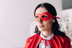 Portrait of attractive super businesswoman. In cape and mask looking away in office stock photos