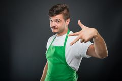Portrait of attractive supermarket employer showing number three Royalty Free Stock Photo