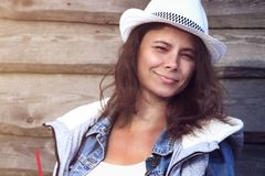 Portrait of attractive tanned young woman in cowboy hat against wooden fence in denim jacket. Beautiful girl in hat. Cute girl smiling Stock Images