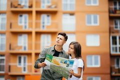 Portrait of an attractive tourist young couple relaxing sightseeing and visiting a destination city on holiday, pointing up and en. Joying traveling together Stock Photos