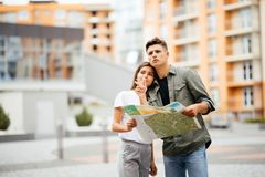 Portrait of an attractive tourist young couple relaxing sightseeing and visiting a destination city on holiday, pointing up and en. Joying traveling together Royalty Free Stock Image