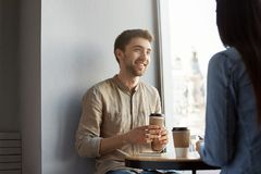 Portrait of attractive unshaved young guy with dark hair, smiling, drinking coffee and listening to girlfriend stories Stock Photography