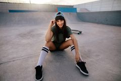 Attractive urban girl sitting relaxed at skate park. Portrait of attractive urban girl sitting relaxed at skate park. Female skateboarder taking break after Stock Photography