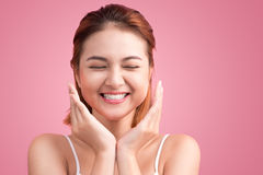 Portrait of attractive Vietnamese woman touching her face. On pink background Stock Images
